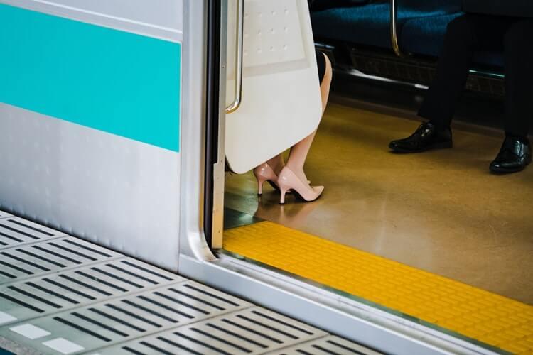 電車に乗って帰宅する女性
